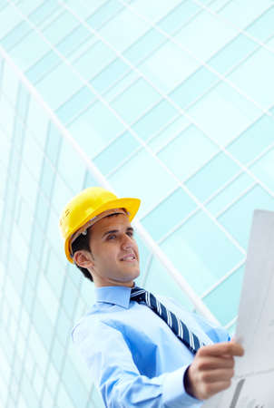 Young engineer looking at paperwork by office building photo
