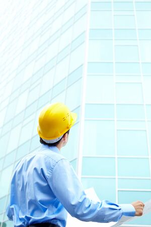 Rear view of engineer looking at office building  photo