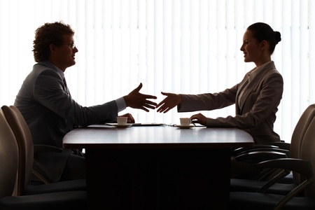 employer: Businessman and businesswoman sitting at table and stretching hands for handshake
