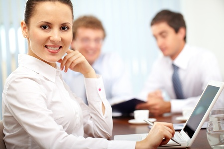 Portrait of a cheerful businesswoman looking at camera against her colleagues  Stock Photo - 9963187