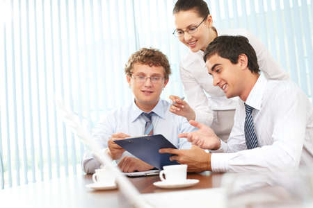 Three business people discussing papers with current results Stock Photo - 9963127