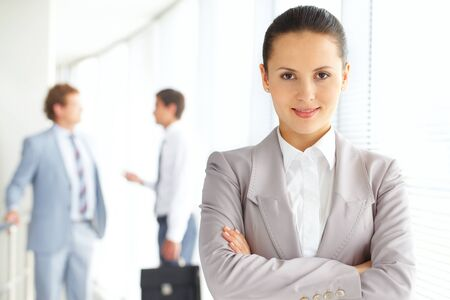 Portrait of an attractive woman against her male colleagues  photo