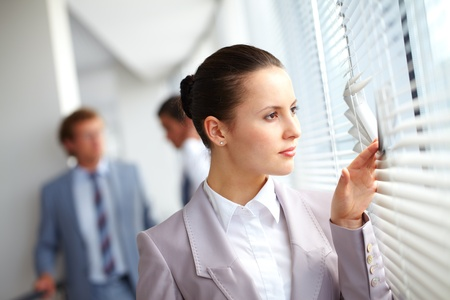 job opening: Businesswoman looking through window against her colleagues