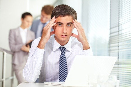Stressed businessman sitting at table and looking at camera Stock Photo - 9963265