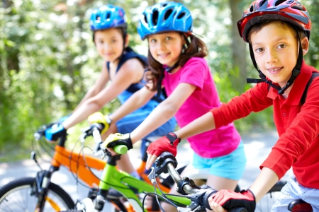 Three little children riding their bikes photo
