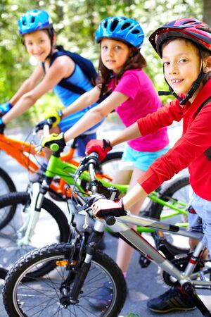 riding helmet: Portrait of three cute cyclists looking at camera and smiling Stock Photo