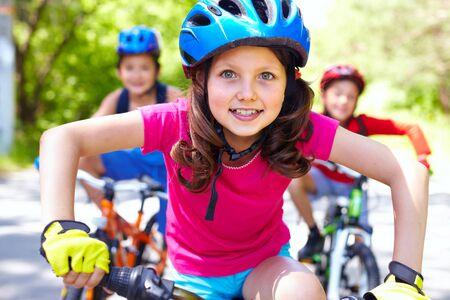 riding helmet: Retrato de una ni�a montando su bicicleta por delante de sus amigos