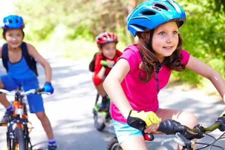 riding helmet: Una ni�a montando su bicicleta con dos amigos detr�s
