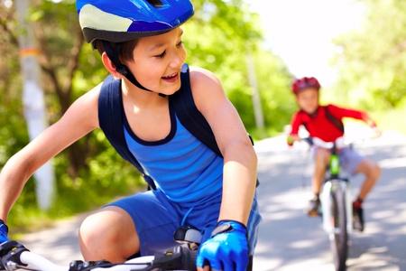 1 つの別のバイクに乗って 2 つの小さな男の子