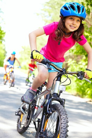 racing bike: A cute girl riding her bicycle with competitors far behind