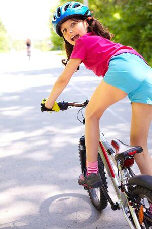 Achteraanzicht van een klein meisje op fiets camera kijken
