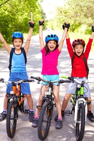 bike ride: Portrait of three happy little cyclists