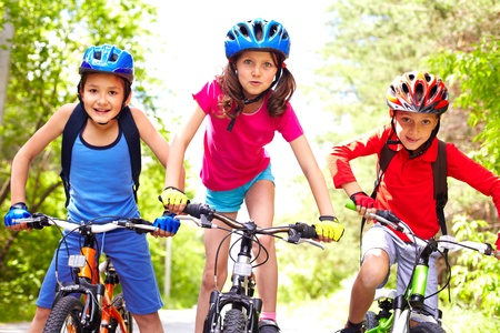 bike riding: Portrait of three little cyclists riding their bikes