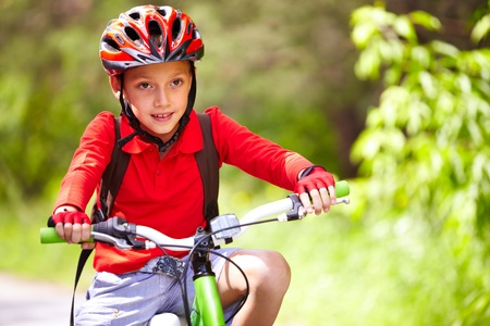 casco rojo: Retrato de un niño lindo en bicicleta