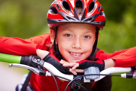 athleticism: Close-up of a little boy�s face on bike looking at camera and smiling