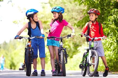 ni�os en bicicleta: Retrato de tres ni�os peque�os con sus motos  Foto de archivo