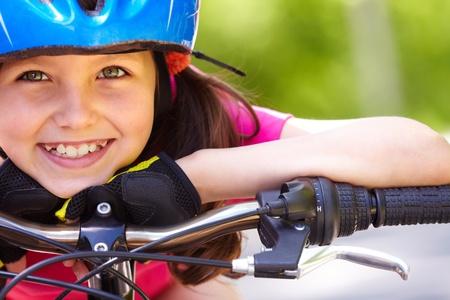 ni�os en bicicleta: Primer plano de la cara de girl?s un poco en bicicleta en c�mara y sonriente Foto de archivo