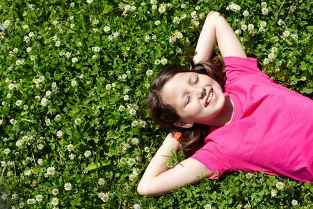 High angle view of a little girl resting on grass  photo
