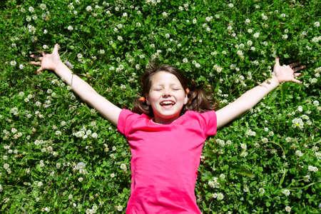 Portrait of a joyful little girl lying on grass Stock Photo - 9963268