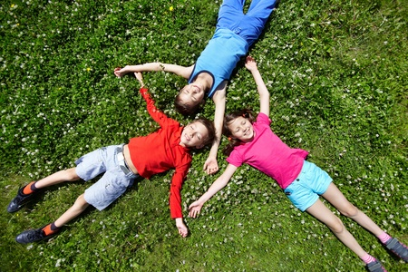Three children having break on grass Stock Photo - 9963272