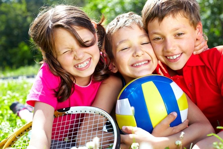 summer sports: Three children with sports equipment embracing, looking at camera and smiling