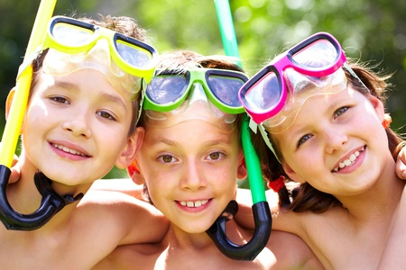 trois enfants: Three children with snorkels looking at camera and smiling Banque d'images