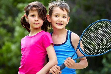 Portrait of a little girl and boy with badminton racket photo
