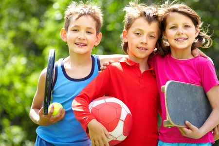 recreation: Portrait of three embracing children with sports equipment