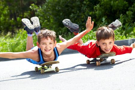 children playing outside: Two little boys lying on their skateboards  Stock Photo