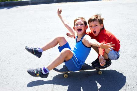 Two cheerful boys sitting on skateboard photo
