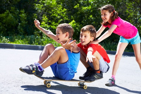 person outside: A girl pushing skateboard with two boys sitting on it