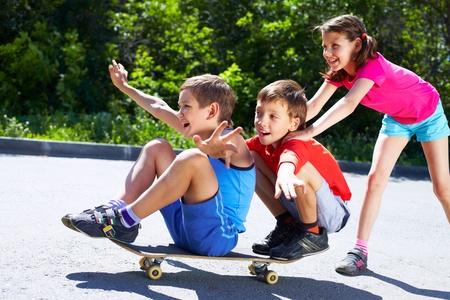 niños jugando en el parque: Una chica empujando patineta con dos muchachos sentados sobre ella