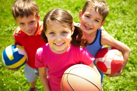 kids football: Portrait of three little children with balls looking at camera and smiling