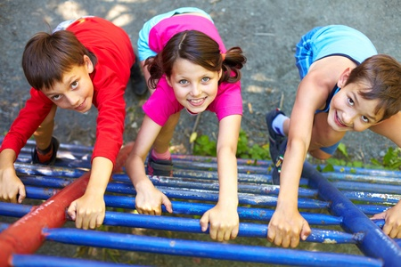 kid friendly: Three little children climbing ladder and looking at camera