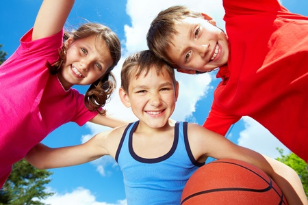 youth sports: Below view of three little friends looking at camera and smiling Stock Photo