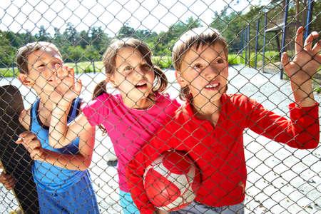 Three children at playground standing behind the netting Stock Photo - 9963271