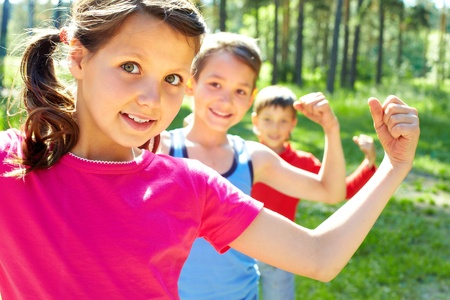 muscle girl: Three little children posing at camera Stock Photo