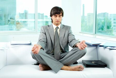A young businessman meditating on sofa in office  photo
