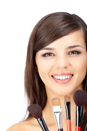 Portrait of a woman with make-up and several cosmetic brushes photo