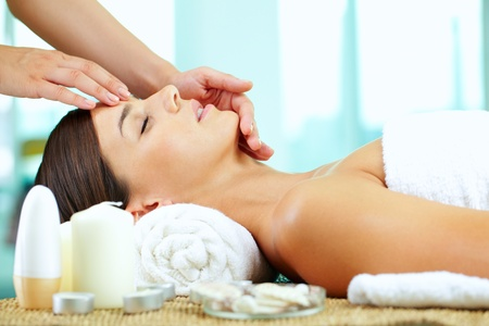 Female hands massaging young woman�s face photo