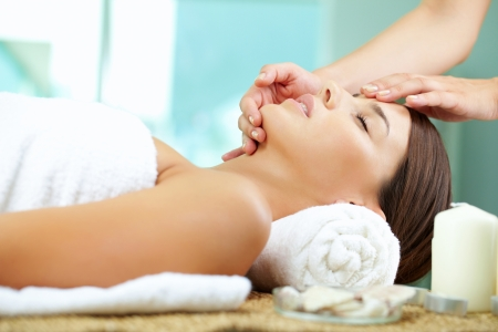 facial spa: Young woman enjoying facial at spa salon