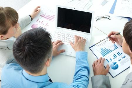 datos personales: Tres personas de negocios que se sientan a la mesa con papeles y un ordenador port�til y la planificaci�n