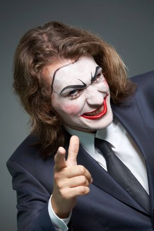 Portrait of businessman with theatrical makeup pointing at camera Stock Photo - 9963158