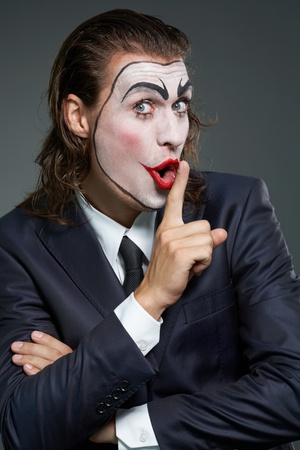 Portrait of businessman with theatrical makeup with finger at lips photo