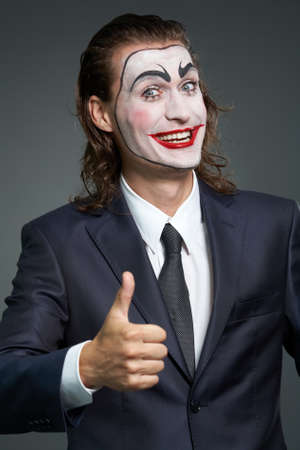 Portrait of businessman with theatrical makeup showing big thumb Stock Photo - 9963164