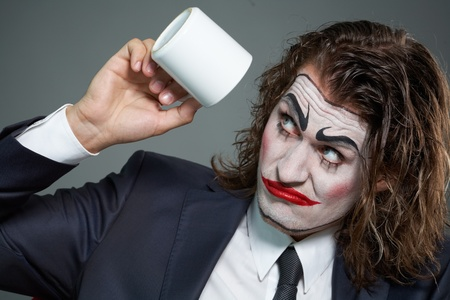 Portrait of businessman with painted face looking at coffee cup Stock Photo - 9963170