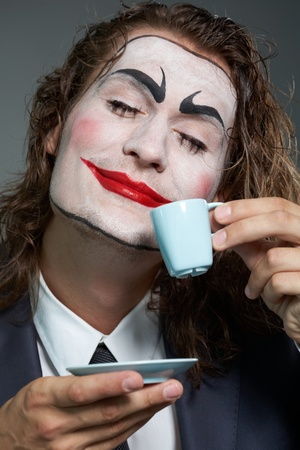 Portrait of businessman with painted face drinking coffee  photo