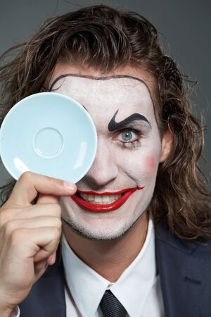 Portrait of businessman with painted face holding a saucer Stock Photo - 9963159