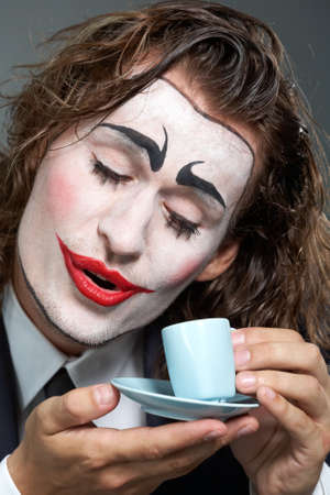 Portrait of man with painted face holding coffee cup  photo