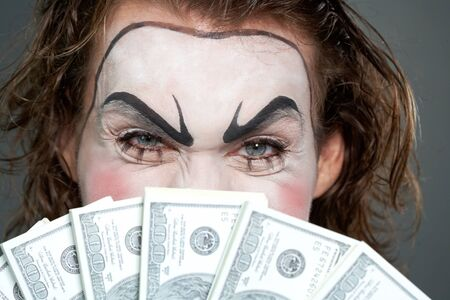 cara pintada: Cara pintada detr�s de varios billetes